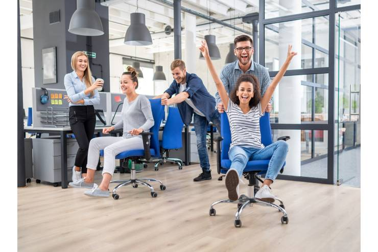 Six people in office sitting on blue chairs and laughing