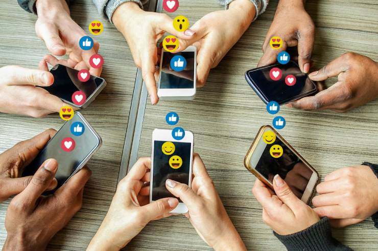Six pairs of hands each holding a phone with emoji images.