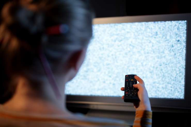 a woman sits in front of a static TV screen