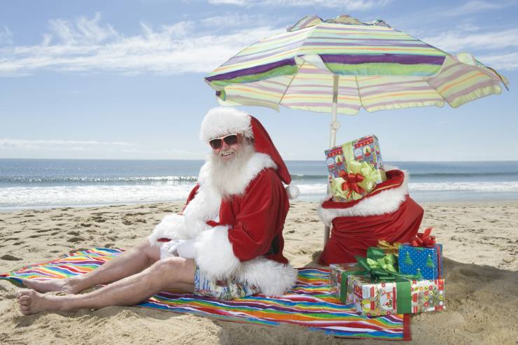 santa sits at the beach on a towel under an umbrella with gifts