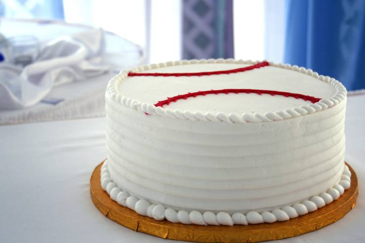a frosted cake decorated like a baseall