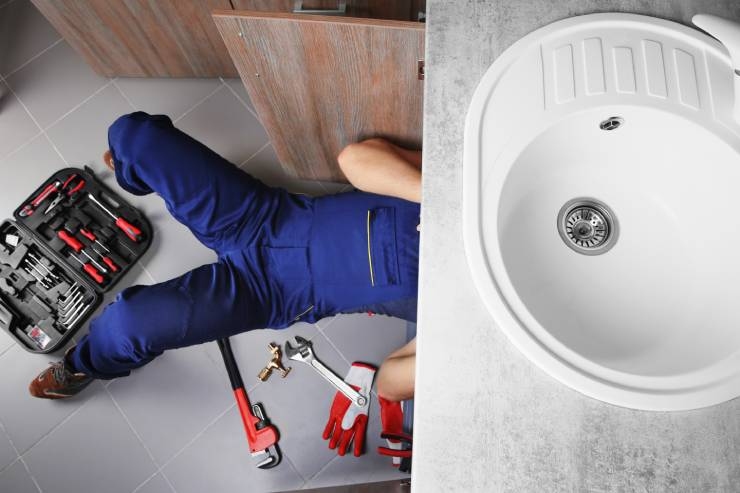 a plumber fixes a sink with his tools scattered about