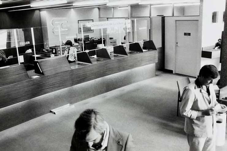 Vintage photo from inside a bank with customers and bank tellers