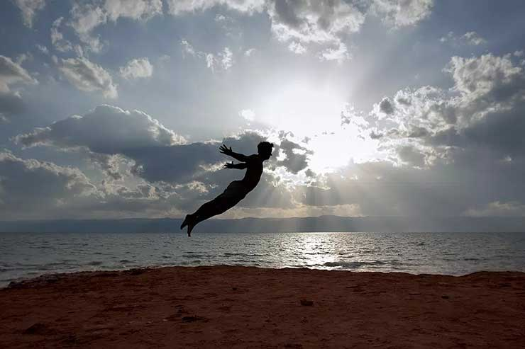 Person recreates visually they are flying in the air above the sand. The ocean is behind with the sun shining through the clouds