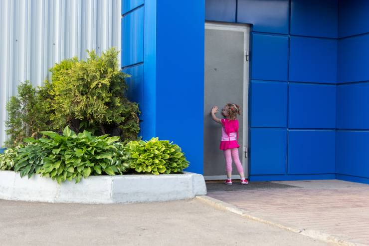 Little girl in pink knocking on gray door with blue walls.