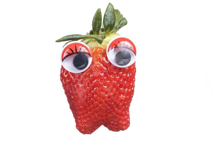 A red strawberry with a green stem and two large googly eyes.