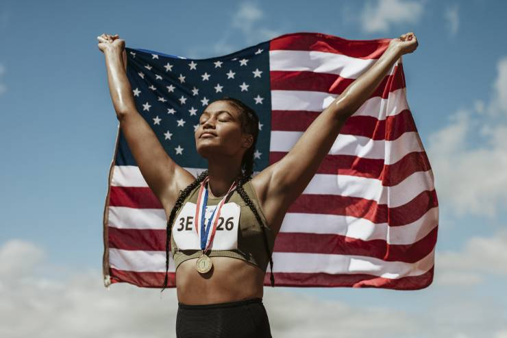 A female olympian with a medal holding a flag up behind her with blue skies in the background.