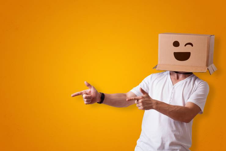 Man with a cardboard box over his face winking and pointing.