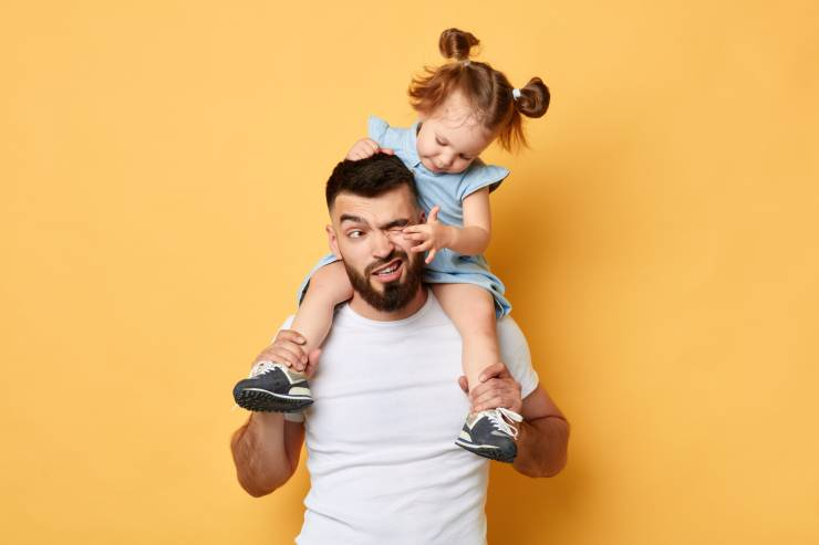 A dad getting his eye poked by his daughter that's sitting on his shoulders.