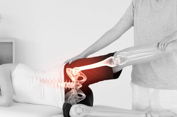 Patient laying on their side with an x-ray view of their lower half during physical therapy.