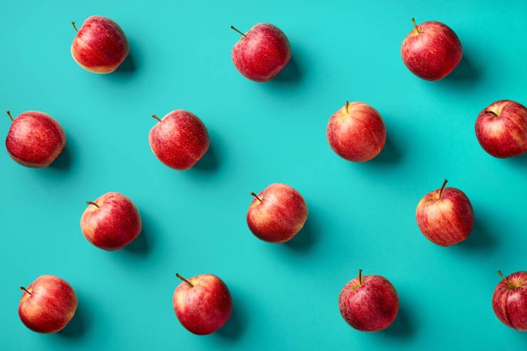 Aerial view of 14 apples spaced out in diagonal rows with a blue background.