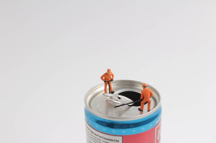 two tiny action figure men pry open a soda can tab
