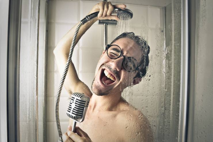 a man in glasses sings with a microphone while in the shower