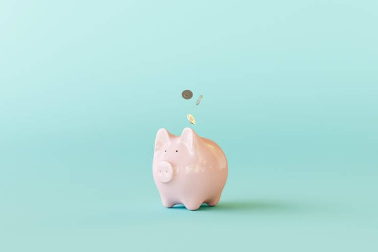 a piggy bank by itself with coins dropping into it