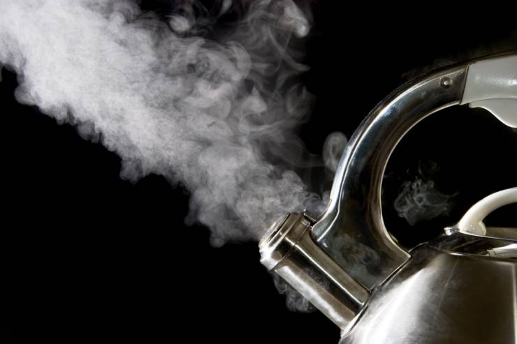 a silver tea kettle is boiling with steam coming out