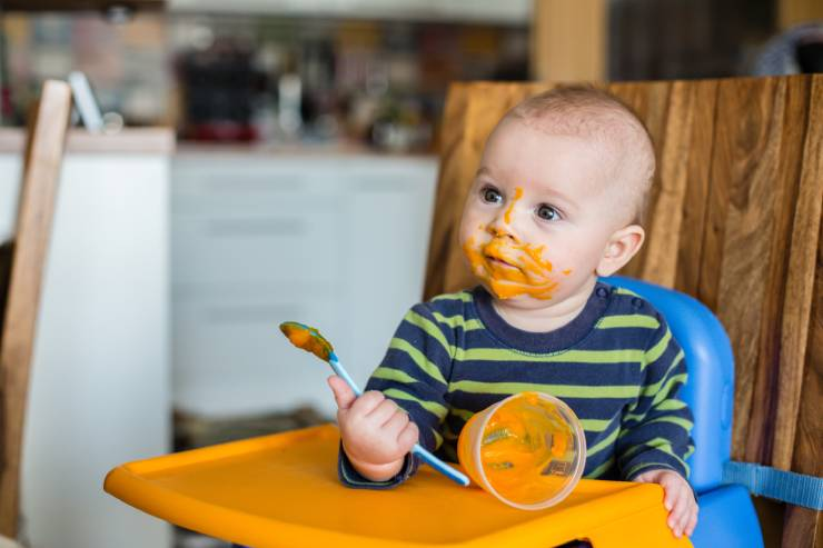 a messy baby sits in a high chair eating pureed sweet potato
