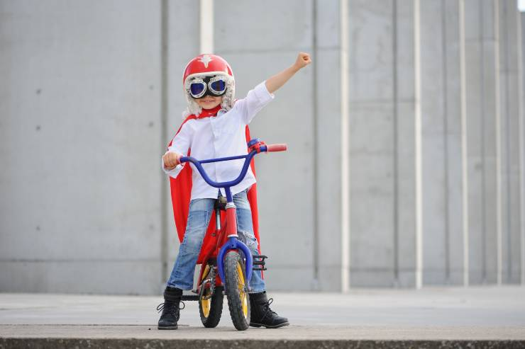 a little kid with a red cape and a helmet and goggles rides a bikeh