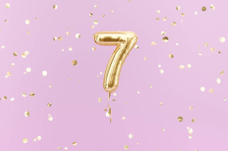 a golden 7 balloon surrounded by gold confetti on a pink backdrop