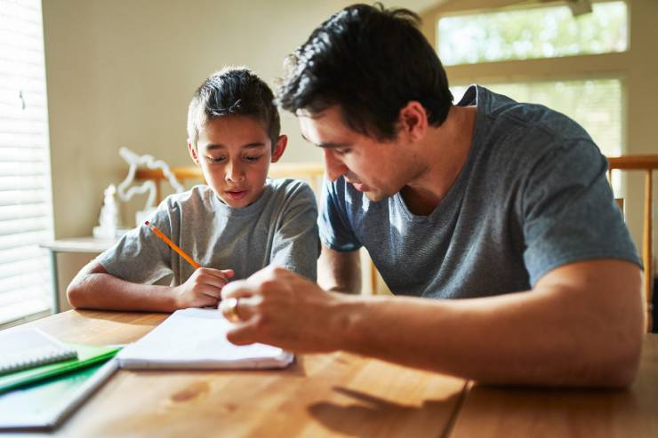a father sits and helps his child with their homework