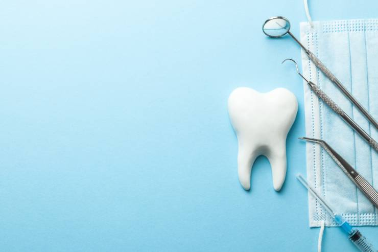 a model of a tooth sits next to dental tools on a face mask