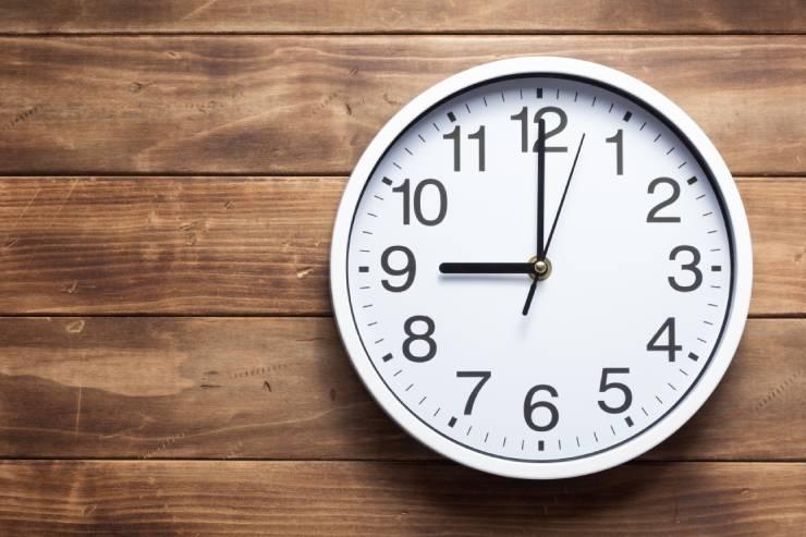 a clock set to 9 o'clock hangs on a wood paneled wall