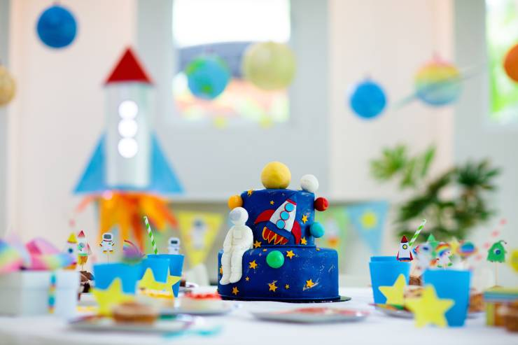 a space-themed kids birthday party with space decorations and a space cake