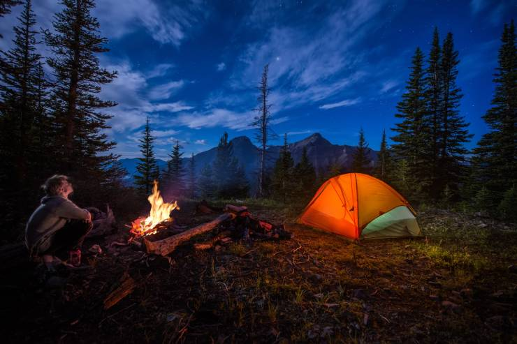 a camper sits by the fire at night with his tent pitched not far off