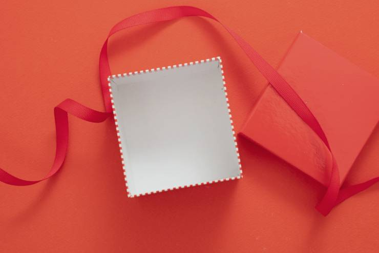 an empty red gift box with a red bow on a red backdrop