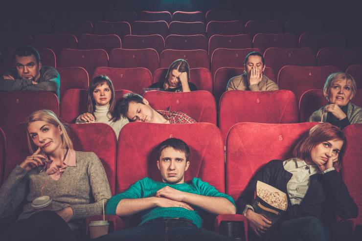 people sit at a movie theater looking bored and unimpressed