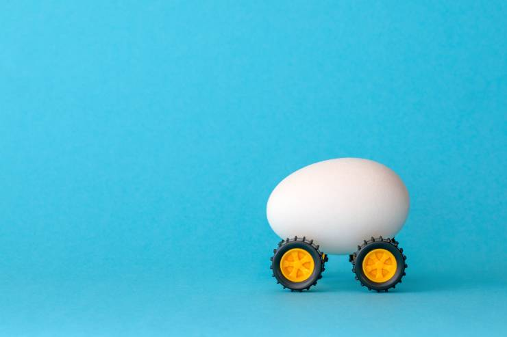 an egg with toy wheels on a blue backround
