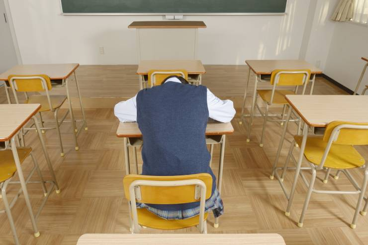 one student sits alone in a classroom with his head on the desk