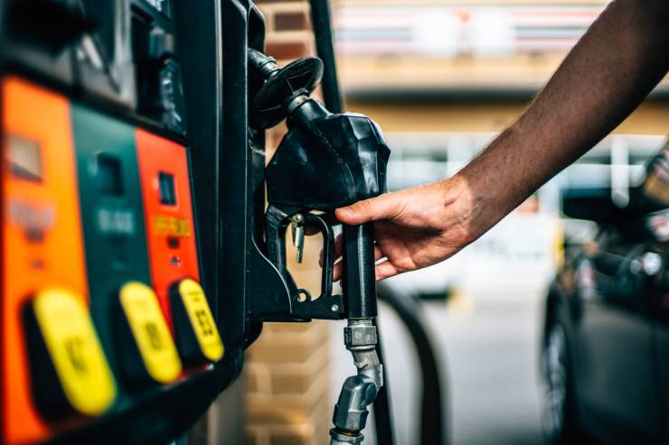 a person grabs the handle of a gas station pump