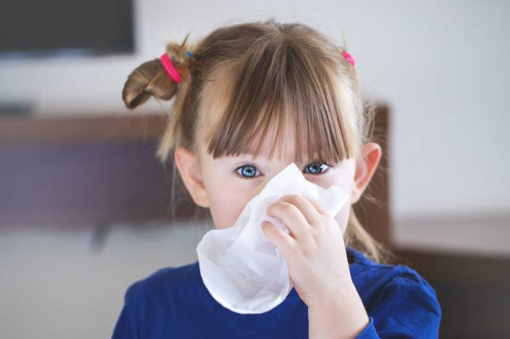 a child wipes their nose with a kleenex