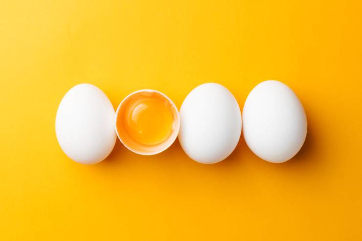 four eggs are lined up on a yellow surface, the second egg is cracked open with the yolk showing