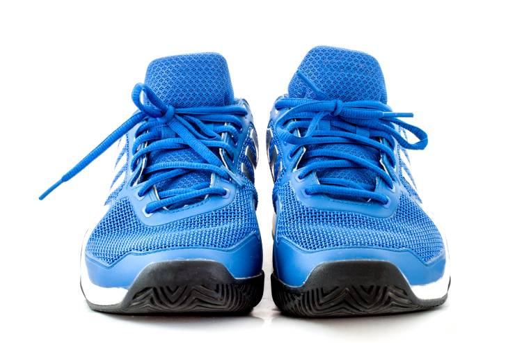 a pair of blue tennis shoes with laces tied