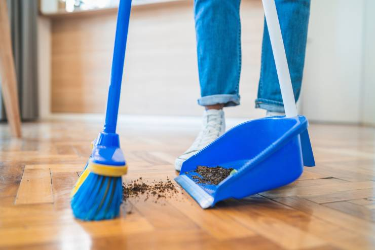 a person sweeps dirt with a blue broom into a blue dustpan