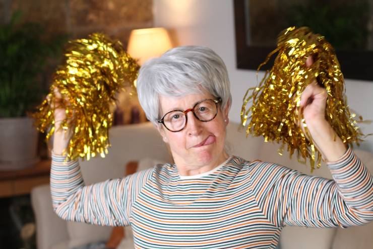 an older person with gray hair and glasses shakes pompoms at the camera while sticking their tongue out