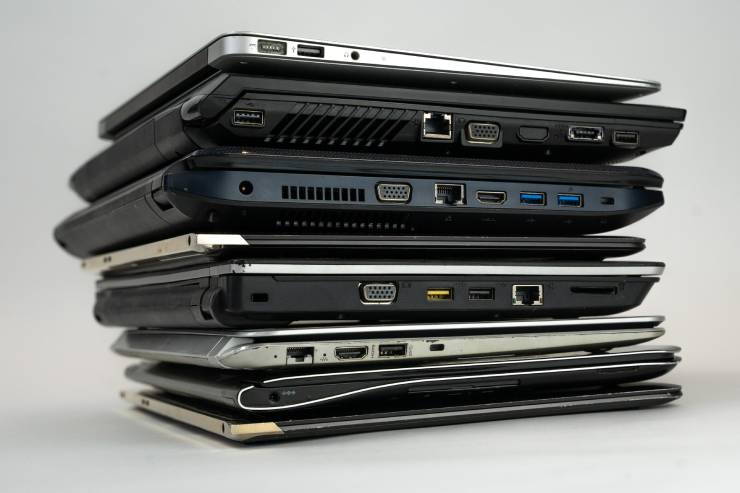 seven laptops stacked on top of one another