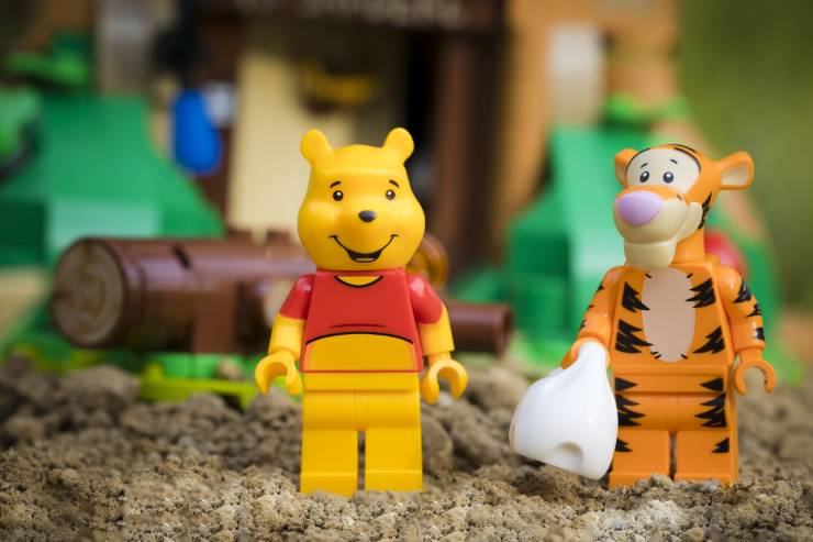 Plastic Toy Figurines of Winnie the Pooh and Tigger in a Sandbox.
