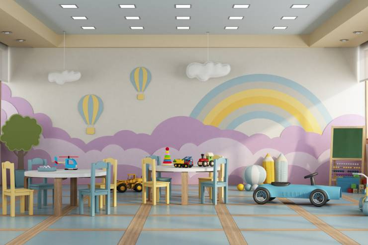 Classroom with Tables and Chairs, Toys, and a Rainbow Mural with Clouds and Hot Air Balloons Painted on the Wall.