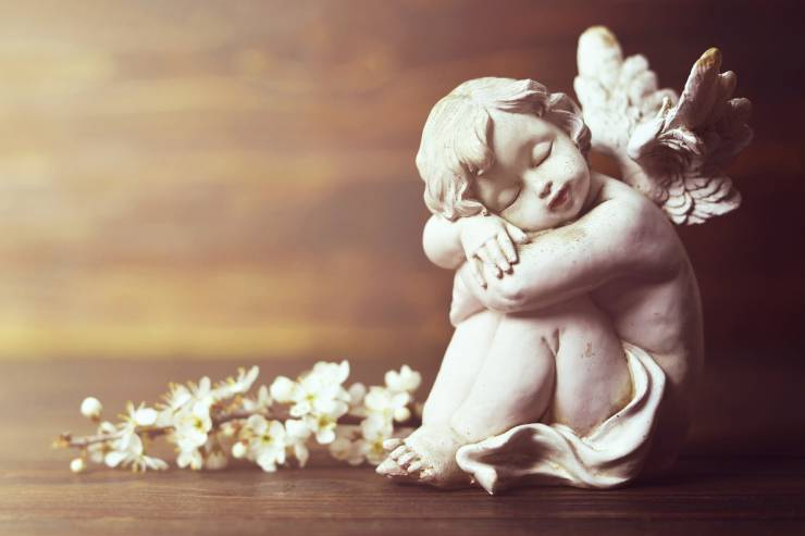 Ceramic Angel Figurine on a Wood Table with a Stem of Flowers Next to it.