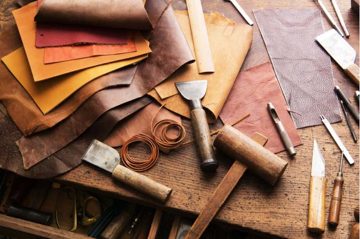 A wood craftsman's table covered in leather scraps and various tools.