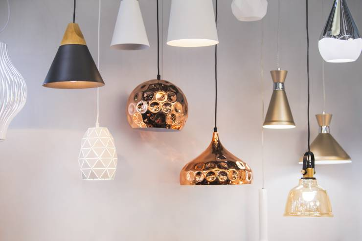 A mixture of various pendant lamps hanging against a white background.