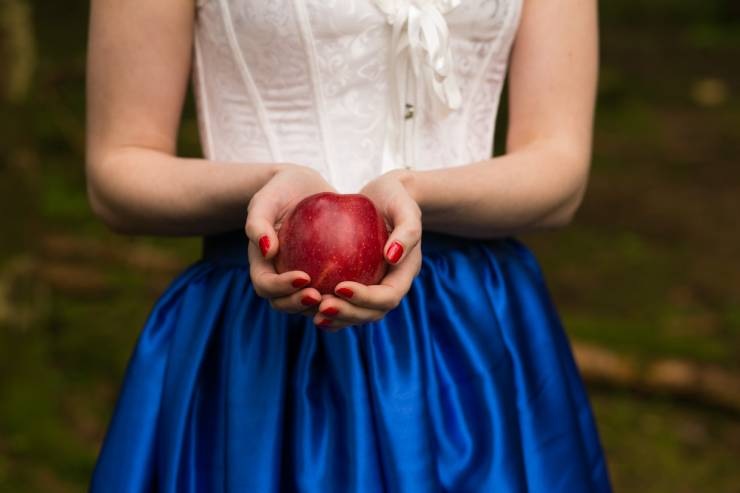 A red apple in the hands of a woman with painted red nails and a satin blue skirt.