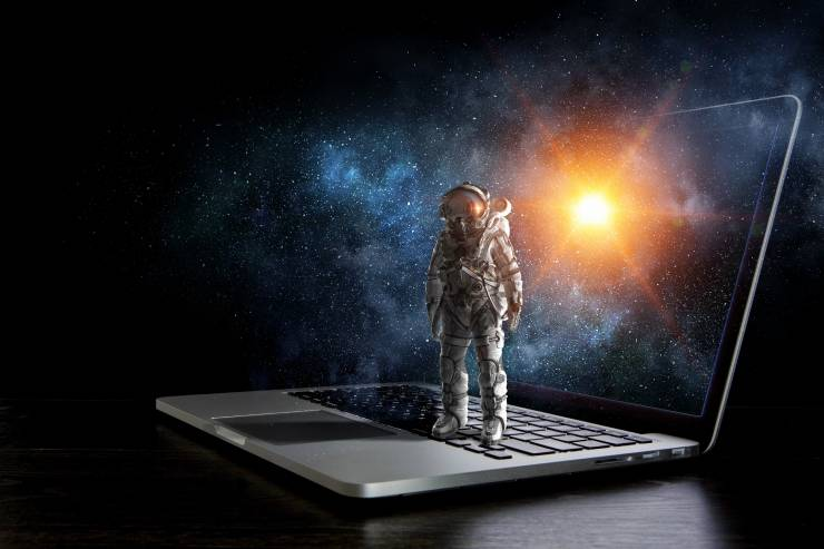 Illustration of a laptop with a miniature spaceman standing on the keyboard, in front of outer-space.