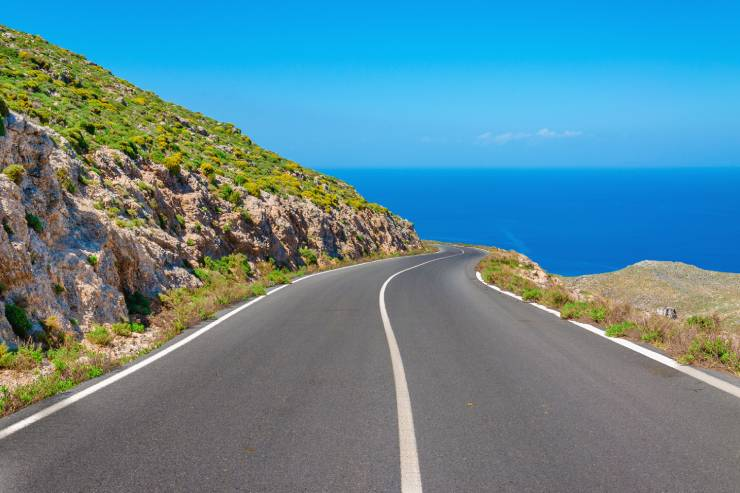 a two-way road between a hillside and an ocean view
