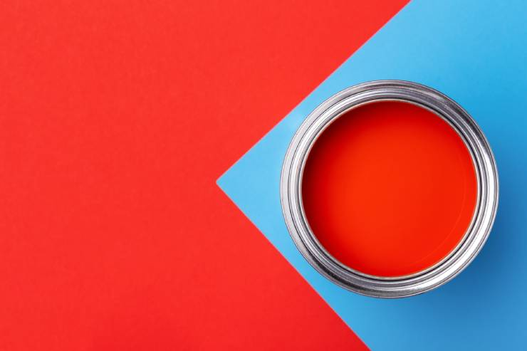 a can of red paint on a red and blue painted surface