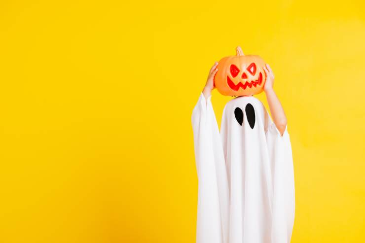a child wearing a ghost costume holds a jack-o-lantern on their head