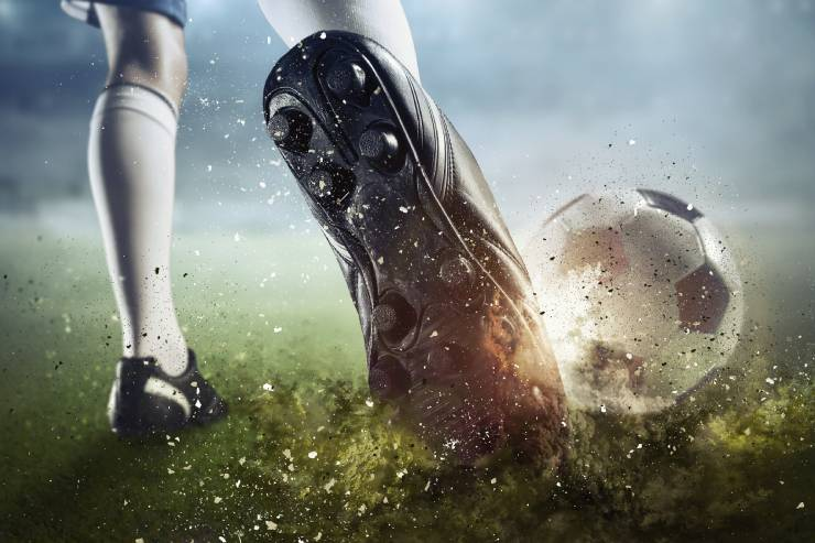 a close-up of a soccer player's legs from behind as they wind up to kick a soccer ball