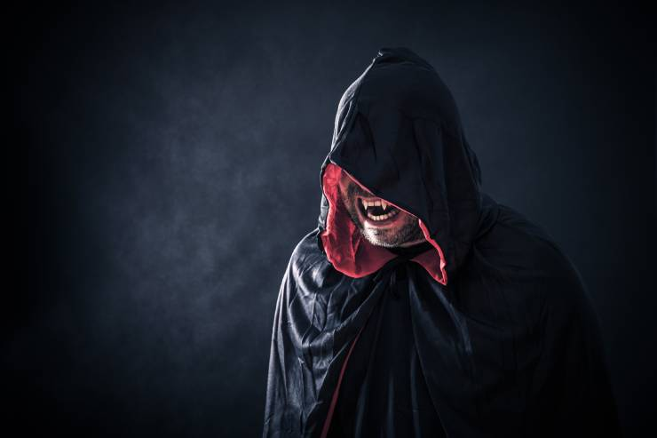 a hooded vampire bares their teeth against a black backdrop